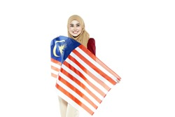 Muslim woman happy holding a Malaysian flag. Malaysia 60th Independence Day.