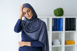 Muslim woman having a severe headache. Female office worker tired and feel bad. Stress and health.