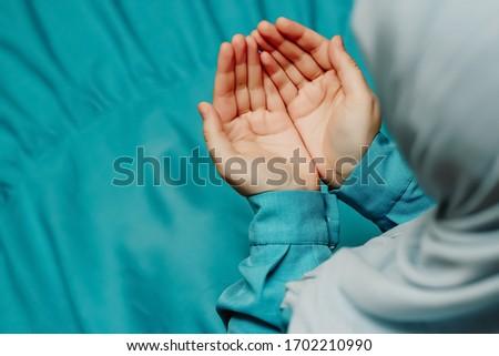 Muslim woman in a headscarf praying (makes a dua) Stok fotoğraf ©