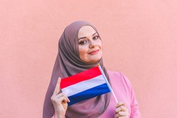 Muslim woman in hijab holds flag of Netherlands