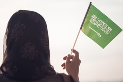 Muslim woman in scarf with Saudi Arabia flag of at sunset.Concept