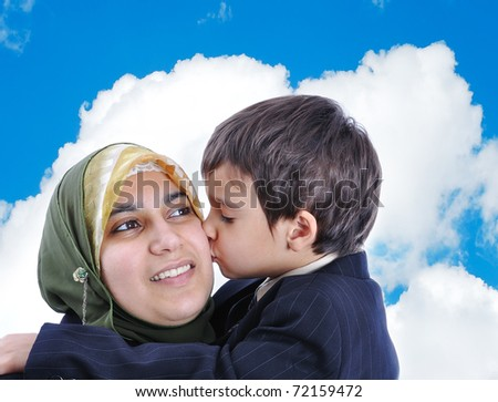 Muslim woman kissing her son - stock photo