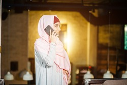 Muslim Woman On Break Using Mobile Phone In cafe