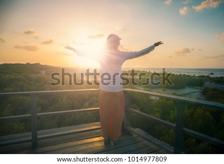 Muslim woman open arm and rise hands up on beautiful nature view. Islam pray on hill fasting ramadan day background. allah support quran standing enjoying sunset concept believe world wisdom 2018 #1014977809