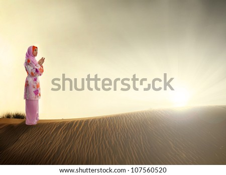 muslim woman praying on the desert