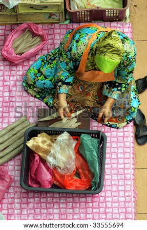 Muslim woman selling fresh vegetables at market in Kota Bharu Mal - stock photo