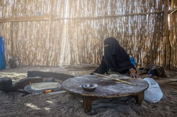 Muslim woman, sitting by the hearth bakes traditional bread for the family