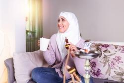 Muslim woman smoking shisha at home and drinking coffee or tea. Muslim young woman enjoying while smoking nargile. Arab girl smoking Hookah