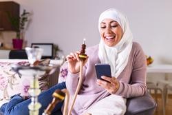 Muslim woman smoking shisha at home and texting with her friends. Muslim young woman enjoying while smoking nargile. Arab girl smoking Hookah