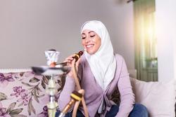 Muslim woman smoking shisha at home. Muslim young woman enjoying while smoking nargile. Arab girl smoking Hookah