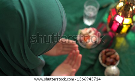 Muslim woman wearing hijab. Holy month of Ramadan. Dua (prayer) for breaking fast and beginning fast. Food and water. Praying, Islam, Religion #1366943714