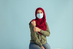 Muslim woman wearing protective face mask showing her arm with band-aid after getting vaccination. Woman in hijab received corona virus vaccine.