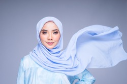 Muslim woman wearing traditional wear and hijab isolated on grey background. Hijab is creatively made flying. Idul Fitri and hijab fashion concept.
