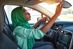 Muslim women are adjusting the rearview mirror of the car. Safety driving woman adjust the car rearview mirror in interior before start travel trip every time. Muslim woman driving a car