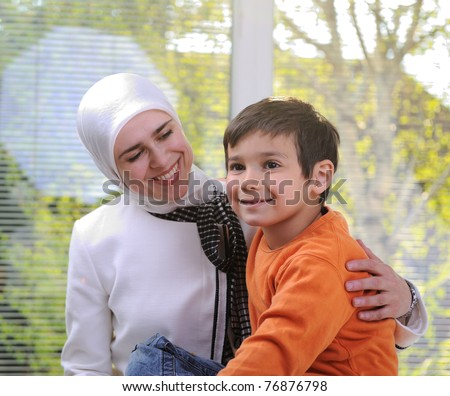 Muslim young woman with little cute boy - stock photo