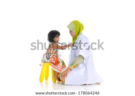 Muslimah female doctor examining little kid, isolate on white background