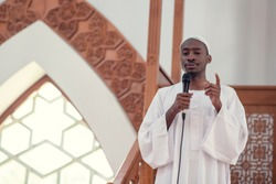 Muslims black african Imam has a speech on friday afternoon prayer in a mosque