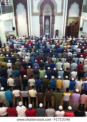 Muslims ready to perform Friday prayers lead by an imam (foreground, middle) in Kuala Lumpur, Malaysia. Male Muslims are compulsory to attend weekly Friday prayers.