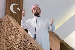 Muslims young arabic Imam has a speech on friday afternoon prayer in mosque. Muslims have gathered for the friday afternoon prayer in mosque and are listening to the speech of imam