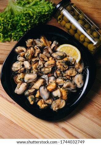 Mussel meat on a wooden Board on a wooden table. Mussel meat with lemon. Mussel meat with lemonFresh raw mussel meat and lemon.