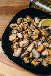 Mussel meat with lemon.  Mussels, molluscs, seaweed, sea plants, mussel meat, healthy food, seafood, gourmet food, Mediterranean cuisine, delicious dish.