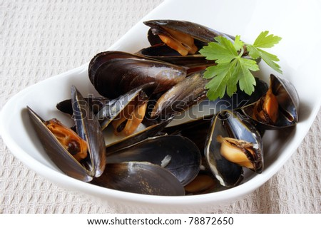 Mussels cooked with white wine sauce in a white bowl