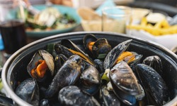 Mussels in a bowl with French fries on a restaurant.  A classic dish in Belgium, France and Netherlands.