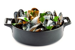 Mussels in a white wine and cream sauce on a table. Classic French meal Moules mariniere isolated on white background.