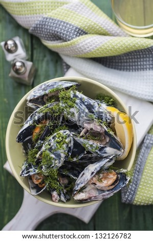 Mussels in cream and bacon on green table