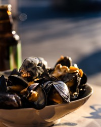 Mussels in the bowl in a white wine sauce. in the street cafe.
