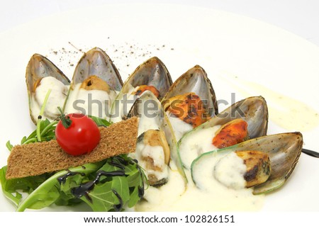 mussels with sauce and greens on a white background