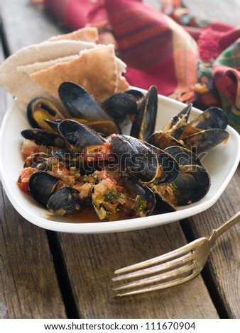 Mussels with wine, tomato and onion sauce, selective focus