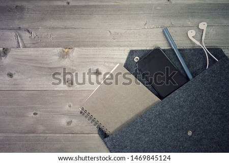Must have, When out of the area, book of environmental protection paper, pen, mobile phone and headphone, put in cloth bags to reduce global warming. Flat lay on real gray wood floor, retro color tone Stock foto ©