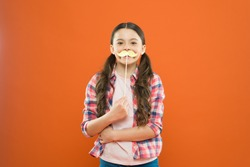Mustache mania. Little child with fake mustache on orange background. Cute small girl holding mustache props on stick. Having fun with photobooth party mustache.