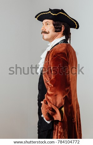 mustachioed eccentric man in the vintage clothes of the baron. Hat tricorn, brown jacket. Funny pigtail hair. man dressed as a courtier