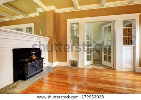Mustard and white empty living room with a hardwood floor and antique black stove