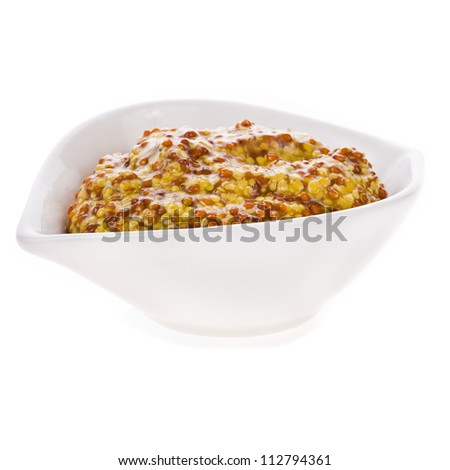 Mustard in a white bowl closeup isolated on white background