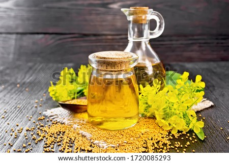 Mustard oil in a glass jar and decanter, mustard grains on a burlap napkin, flowers and leaves on wooden board background Сток-фото ©