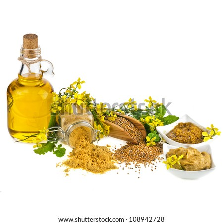 Mustard oil jar and powder spoon, seeds scoop with fresh mustard flower on white