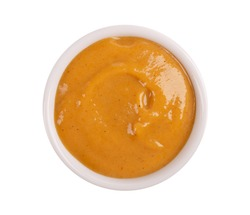 Mustard sauce in bowl, isolated on white background. Honey mustard salad dressing. Top view.