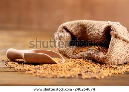 Mustard seeds in bag on  wooden background #240254074