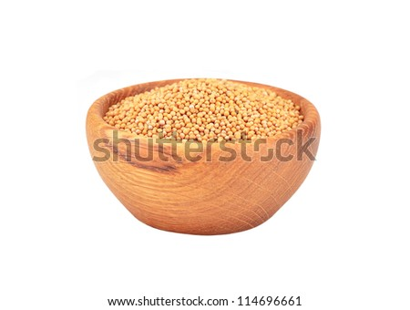 Mustard seeds in wooden bowl, isolated on white background