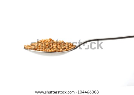 Mustard seeds on a teaspoon isolated on white