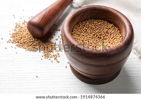 Mustard seeds with wooden mortar and pestle on white table, closeup Foto stock ©