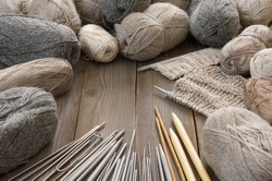 Muted natural cotton, linen, rough woolen yarn and set of assorted knitting needles on rustic wooden background.