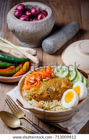 Mutton chicken beef briyani with traditional salad carrrot cucuber boiled eggs sides served in authentic copper clay utensils with raita, gravy and curry shot under natural studio light with nobody