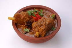 Mutton curry or Lamb curry,spicy and delicious dish garnished with coriander leaf ,red chilli  and star anise  spice in an earthenware bowl with white background.