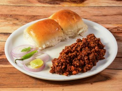 Mutton Kheema pav or keema Pav is a spicy curry dish made up of minced mutton cooked with onion, tomatoes, served with buns or pav, isolated over a rustic wooden background, selective focus