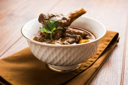 Mutton OR Gosht Masala OR indian lamb rogan josh with some seasoning, served in a ceramic bowl over moody background, selective focus