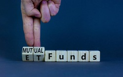 Mutual funds vs ETF symbol. Businessman turns cubes and changes words 'ETF, Exchange-Traded Fund' to 'Mutual funds. Beautiful grey background, copy space. Business and ETF vs mutual funds concept.